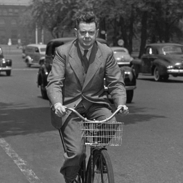 Music Director and Conductor of the Toronto Symphony Orchestra, Sir Ernest MacMillan riding a bicycle along University Avenue.  Photograph was taken by the Toronto Star in June, 1942 as he was leaving the Toronto Conservatory of Music for lunch.